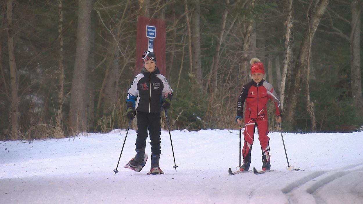 Deux jeunes, en ski de fond et en raquette, dans les Sentiers du Moulin à Lac-Beauport
