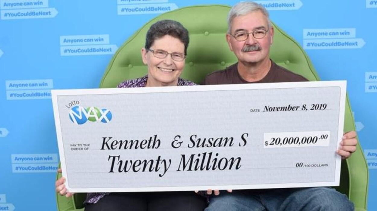 Ken et Susan Salter sont assis sur un sofa vert tenant devant eux un gros chèque de 20 millions de dollars.