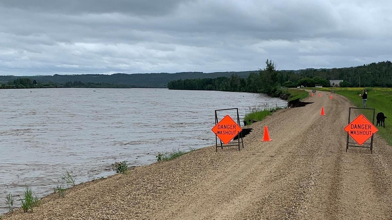 Une route le long de la rivière est jonchée par des cônes et des panneaux qui signalent « Attention : affaissement ».