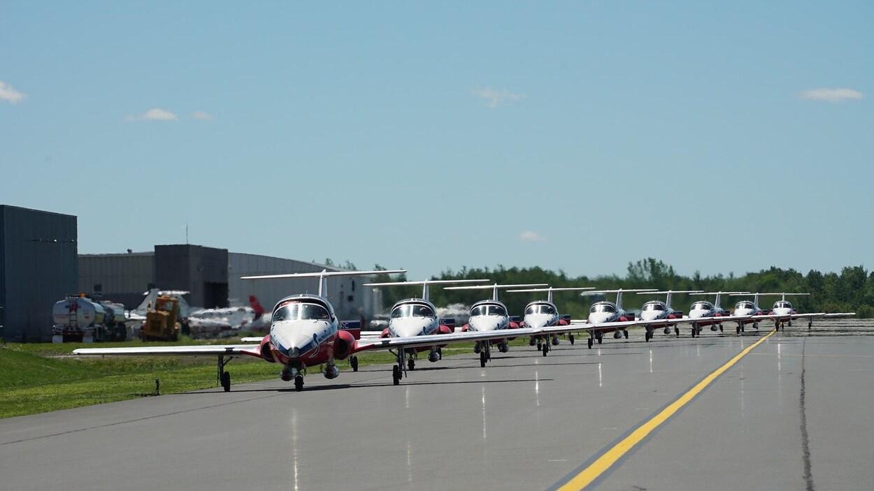 Plusieurs avions des Snowbirds sur une piste d'atterrissage.