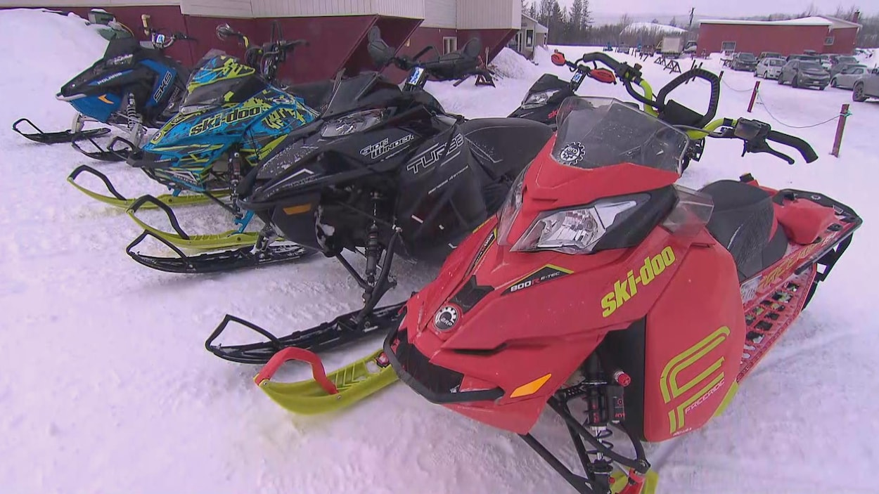 Des motoneiges stationnées dans la neige.