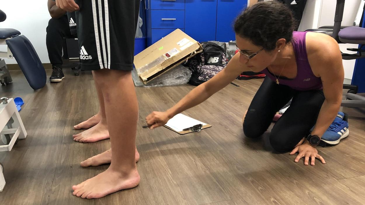 Anne-Laure Ménard, étudiante au postdoctorat en biomécanique, mesure les pieds de deux jeunes joueurs de soccer dans le cadre d'une étude.