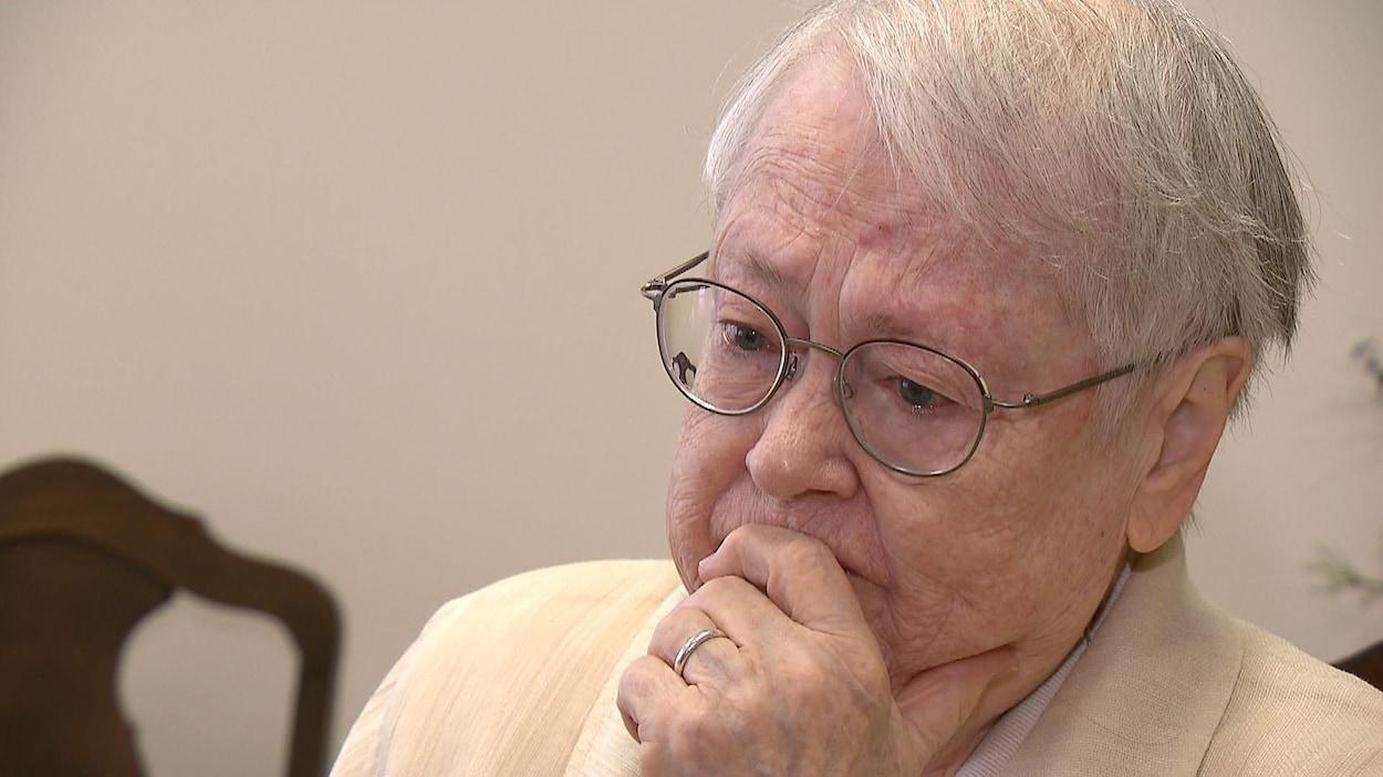 Plan rapproché de Sœur Jacqueline Brisson. Elle porte des lunettes et a les yeux rougis par les pleurs.