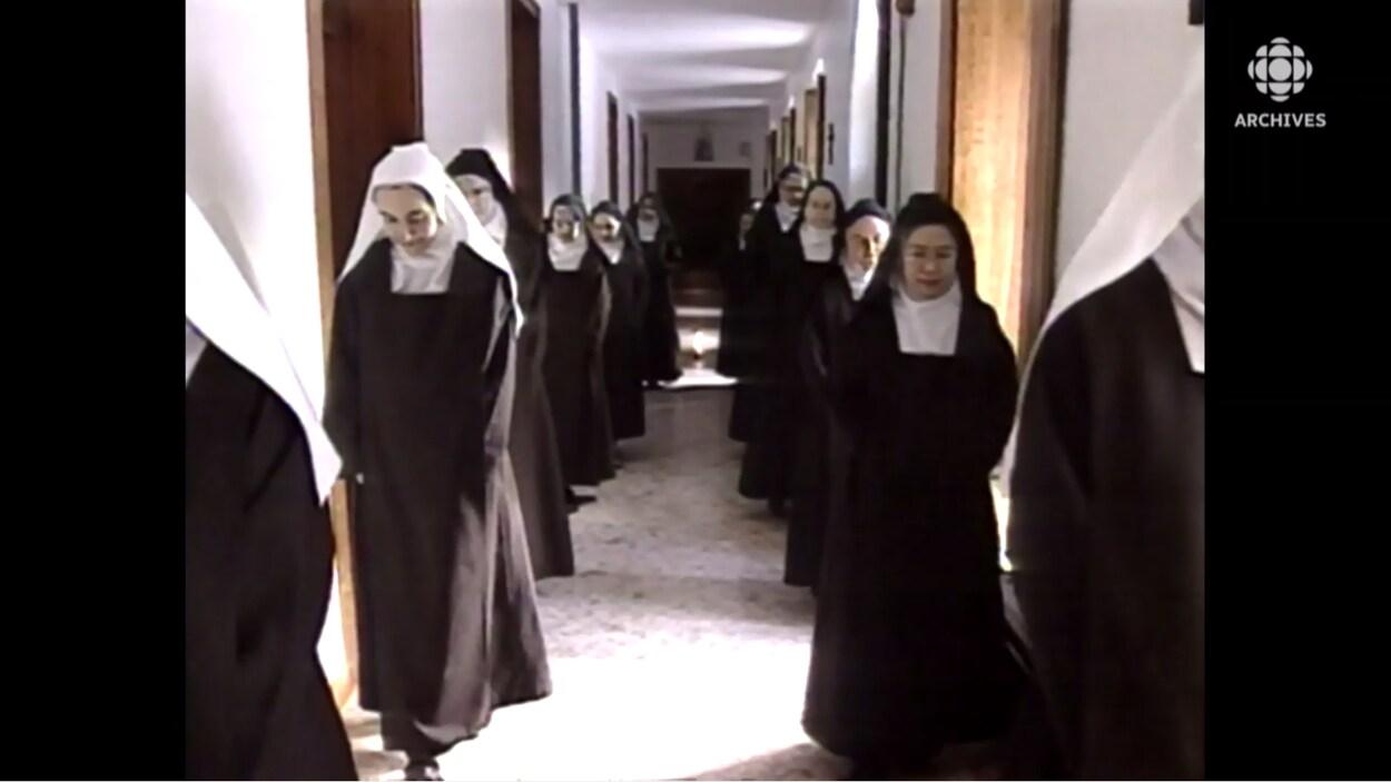 Soeurs carmélites qui marchent dans un couloir.