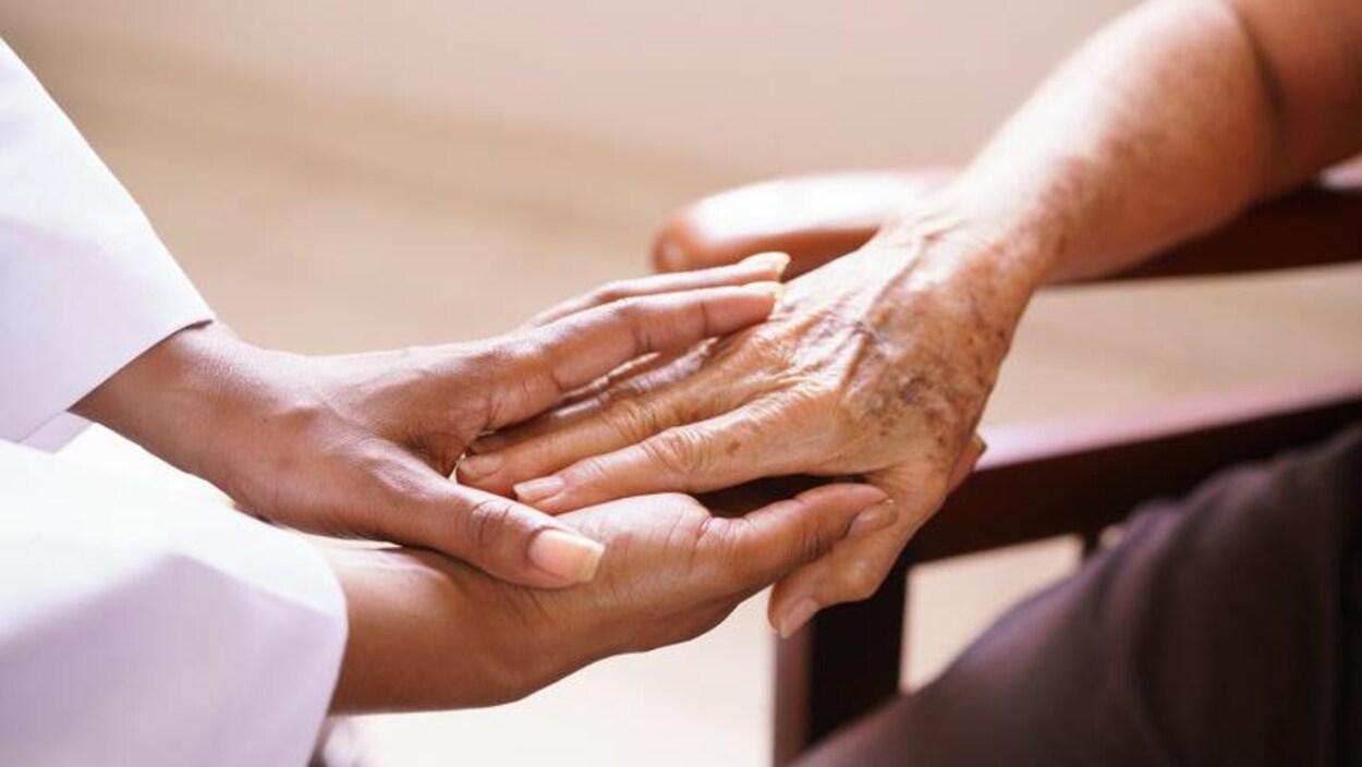 Une préposée tient la main d'une personne âgée
