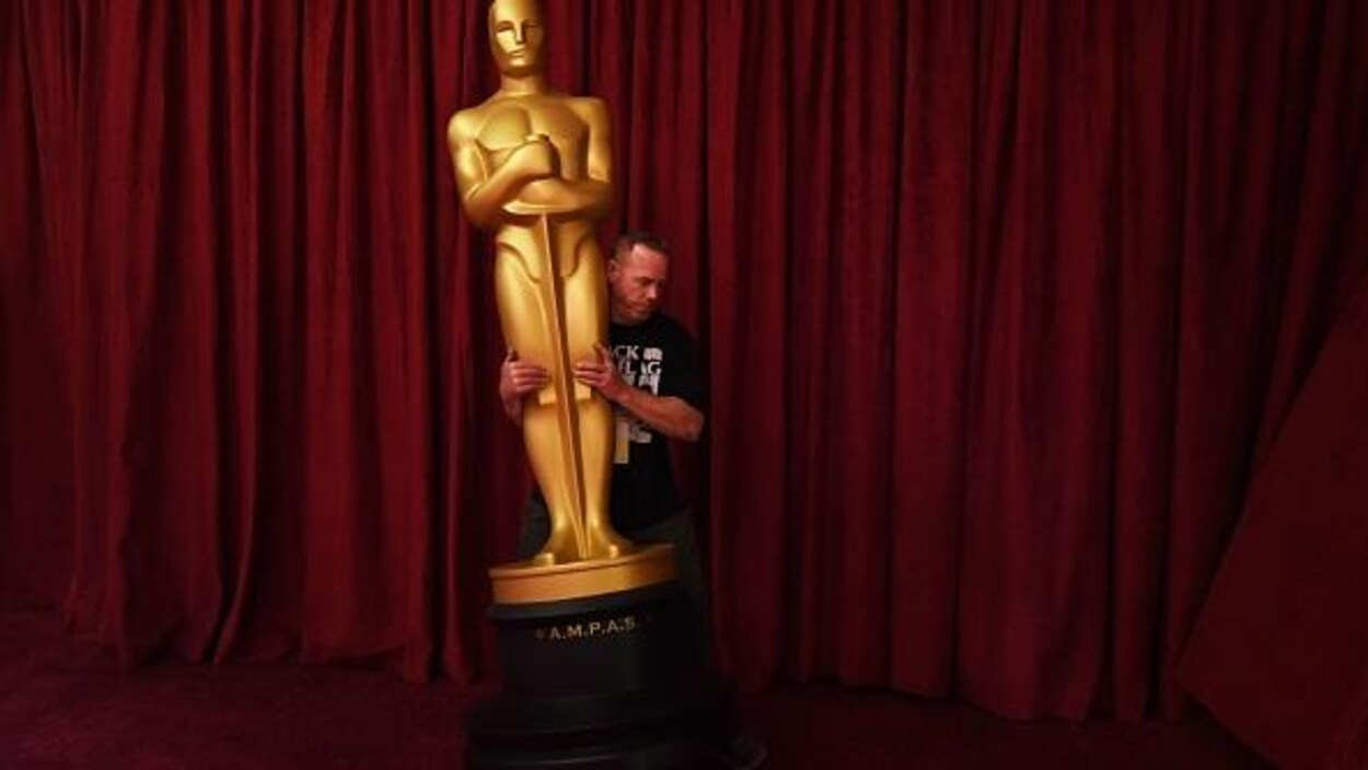 Un homme soulève un Oscar géant.