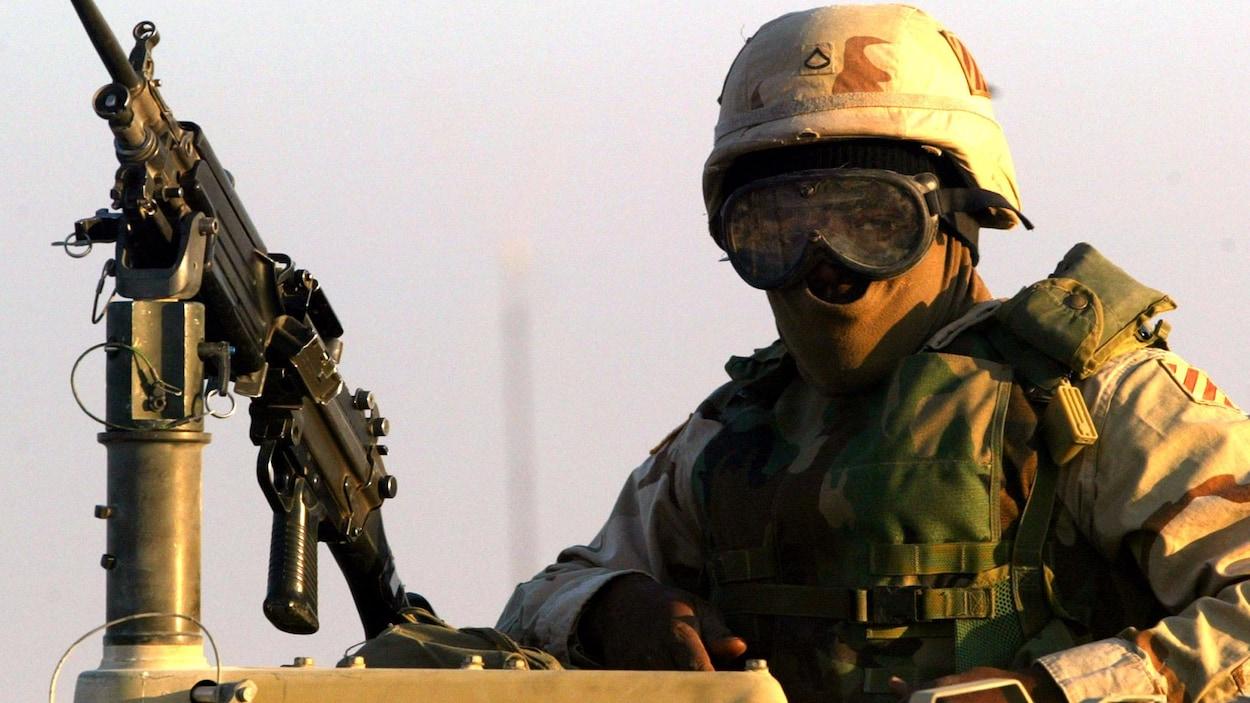 Un soldat américain portant casque, cagoule et lunettes se tient sur un véhicule d'assaut, devant une mitraillette.