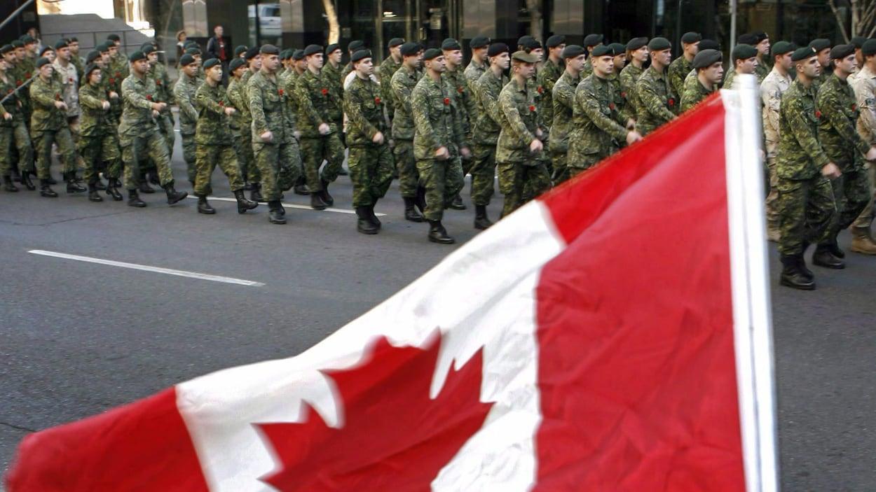 Des militaires portant l'uniforme des Forces armées canadiennes défilent à proximité d'un drapeau du Canada.