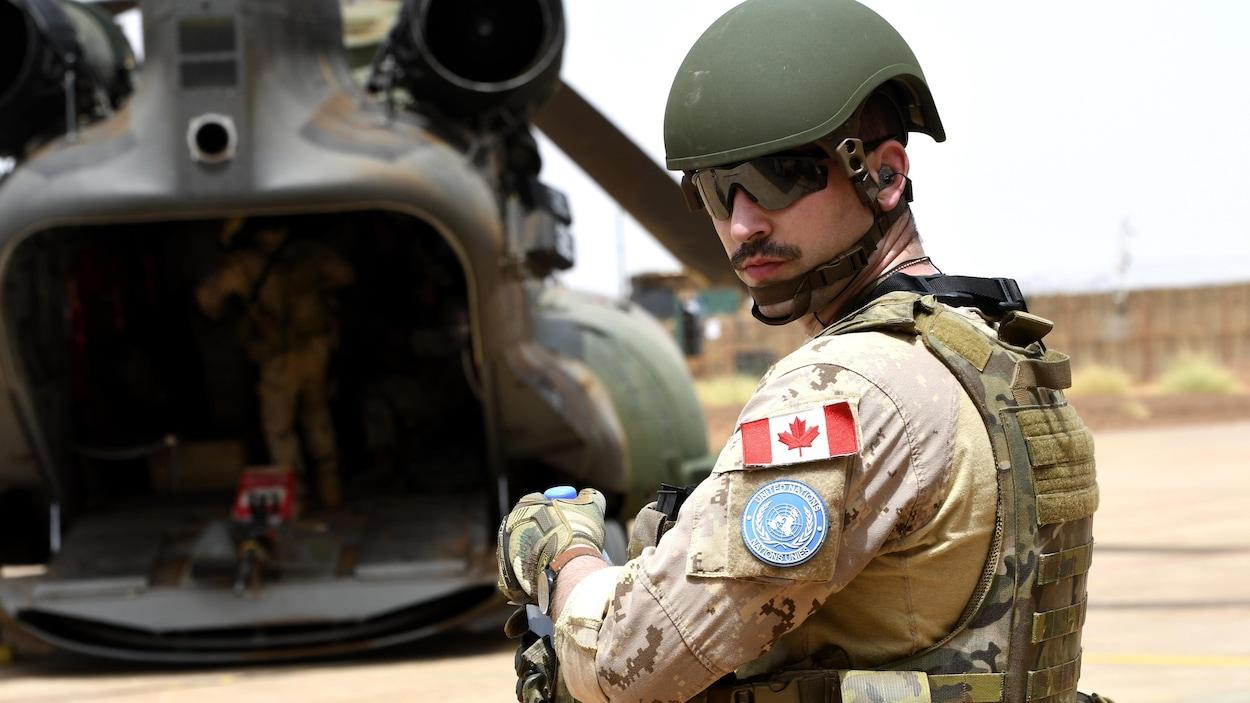 Un soldat canadien portant tout son équipement et des lunettes fumées, près d'un hélicoptère dont la porte arrière est ouverte.