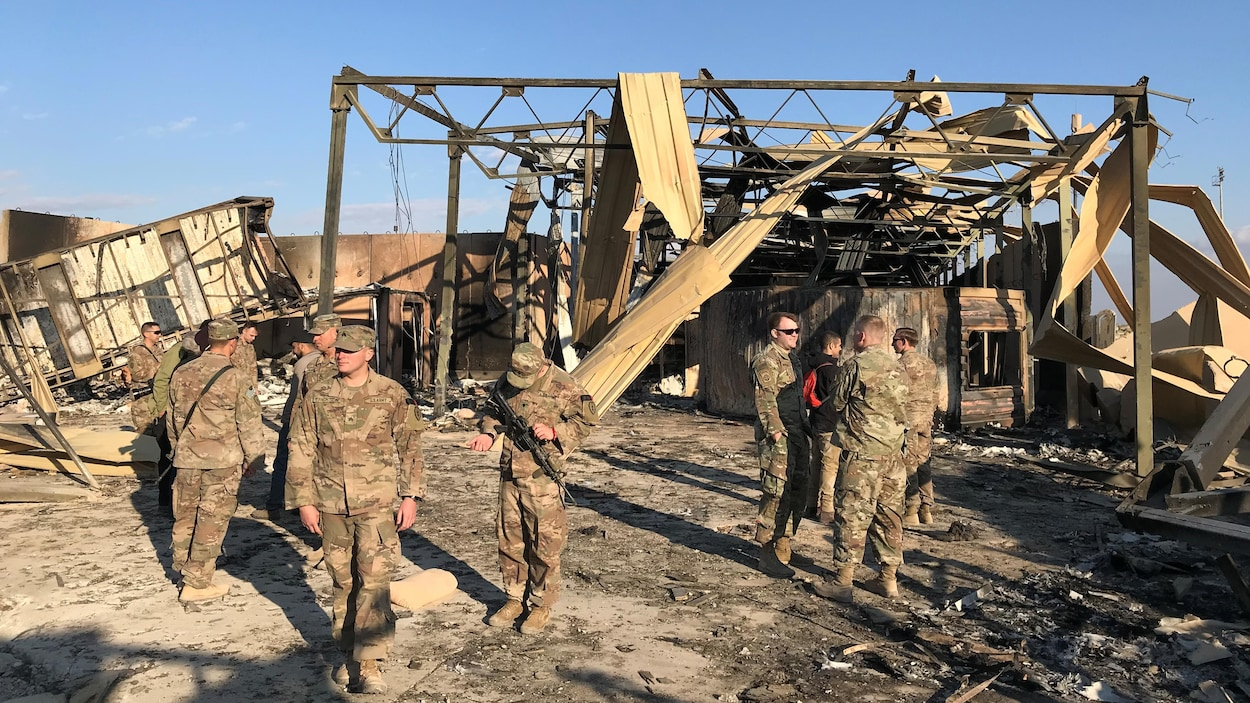Plusieurs soldats discutent près de la carcasse d'une structure.