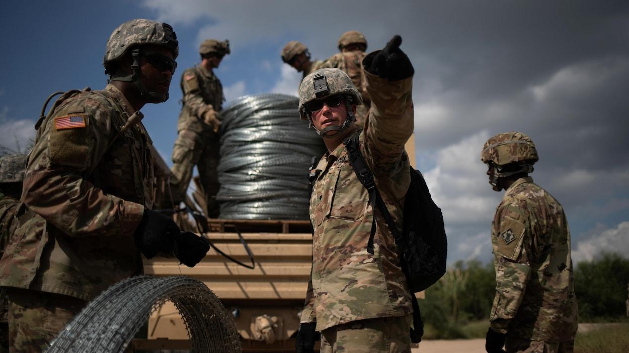 Des soldats transportent du fil barbelé.