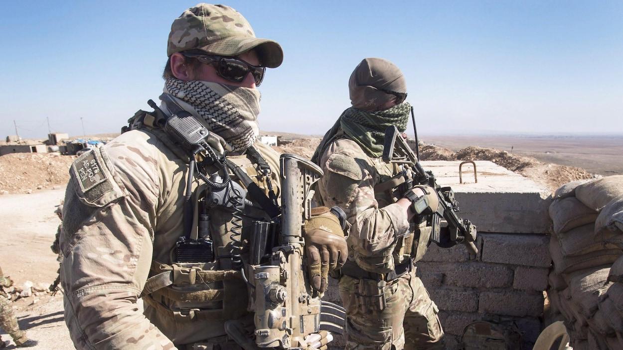 Deux soldats montent la garde dans une position renforcée dans le désert.
