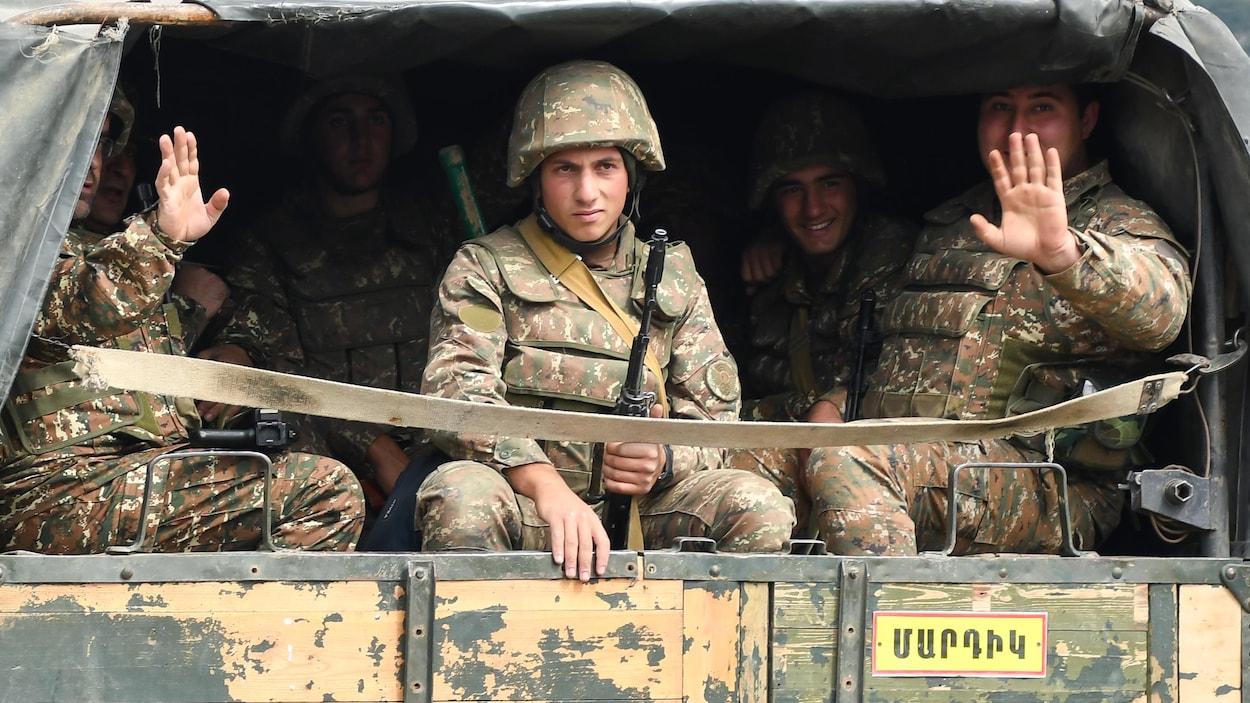 Cinq hommes en treillis militaire sont assis dans la boîte d'un camion.