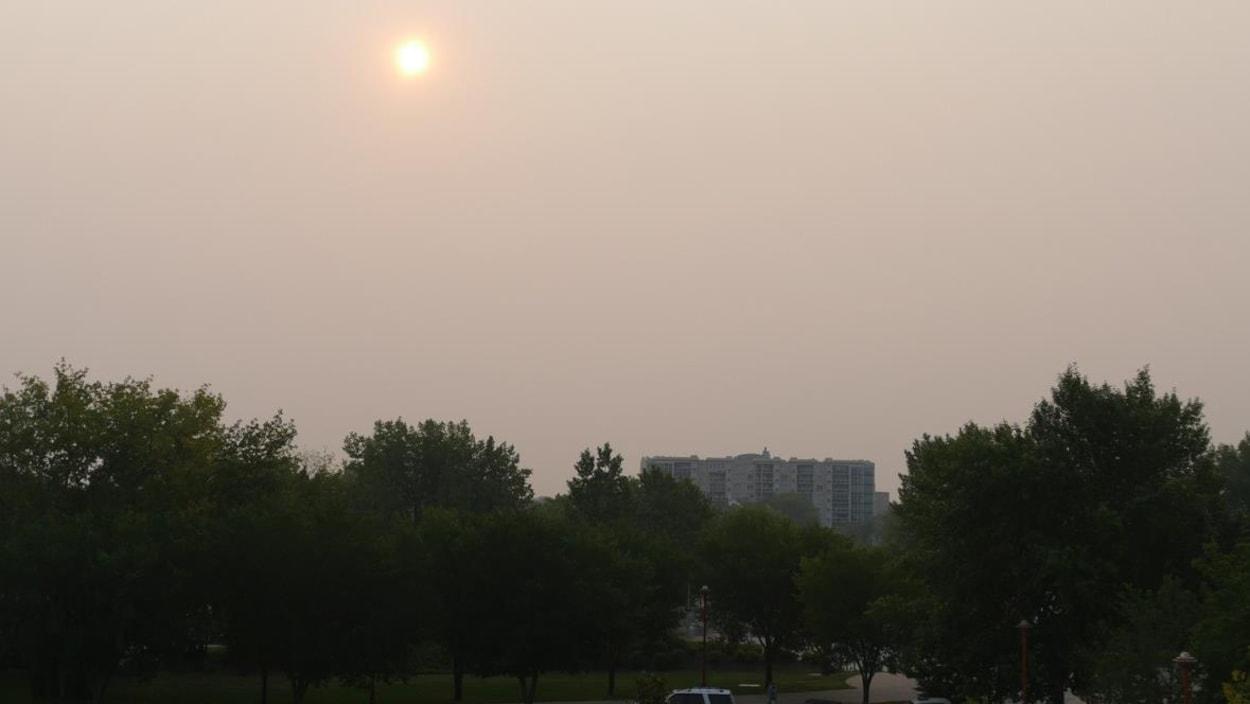 Le soleil est difficilement visible derrière la fumée des feux de forêt à Winnipeg