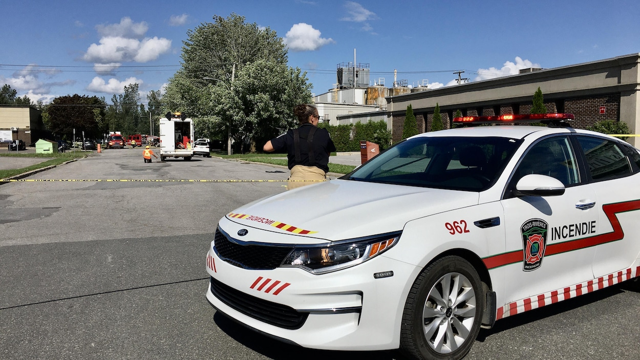 Une voiture des services incendie avec un pompier devant et un périmètre de sécurité à l'arrière-plan.