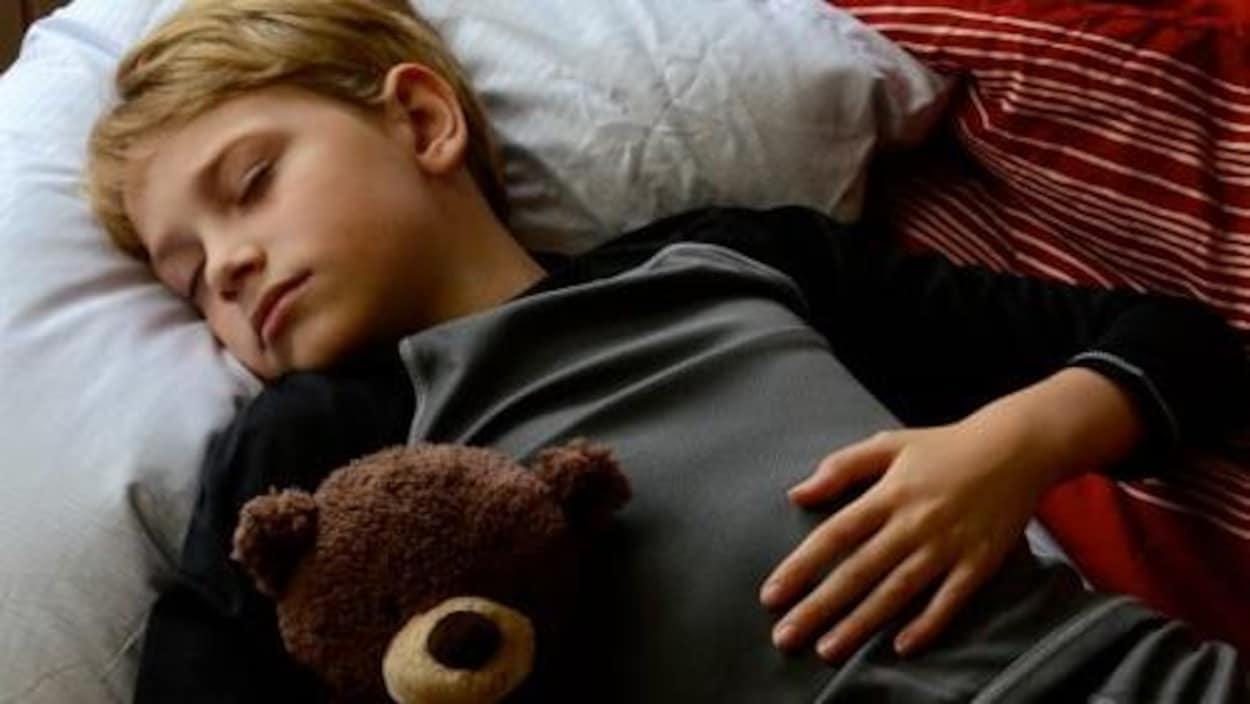 Un garçon d'environ 12 ans qui dort avec un ourson en peluche.