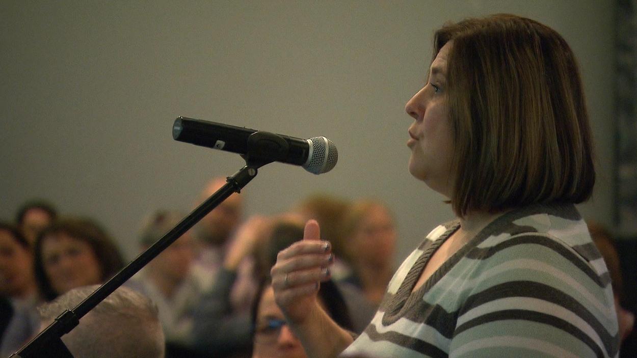 Une travailleuse de la santé au micro pour prendre la parole au Sommet pour trouver des solutions à la pénurie de main-d'œuvre qui sévit dans le réseau de la santé nord-côtier.