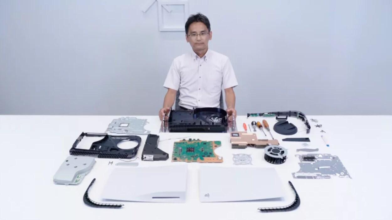 Un homme devant une table blanche sur laquelle sont posés des morceaux d'une console de jeux vidéo.