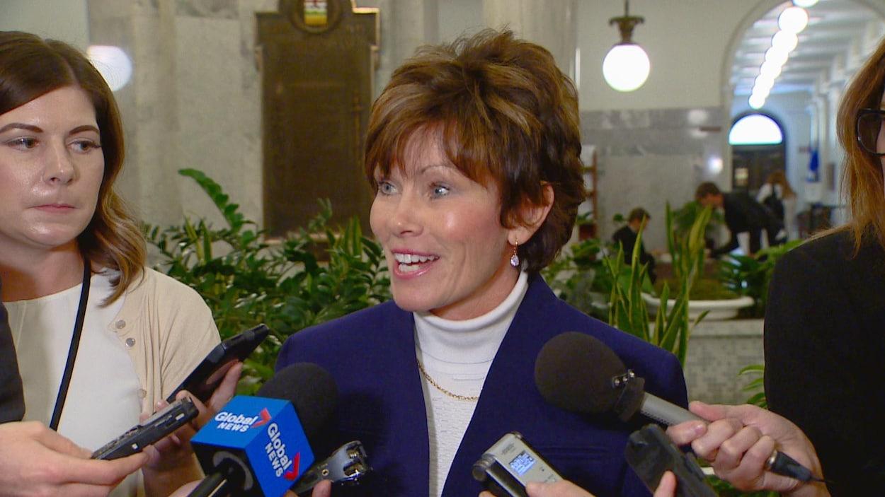 Sonya Savage en mêlée de presse dans les couloirs de la législature. Elle sourit.