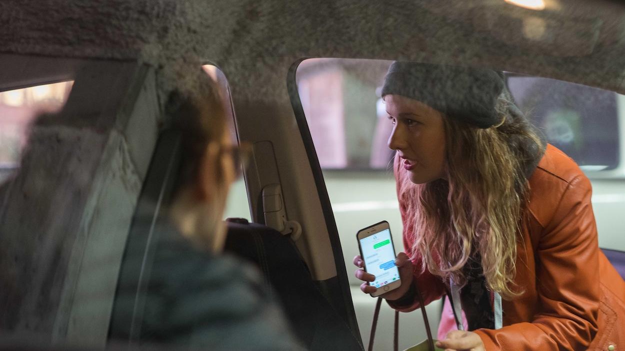 Une femme tient un téléphone cellulaire dans ses mains alors qu'elle rentre dans une voiture.