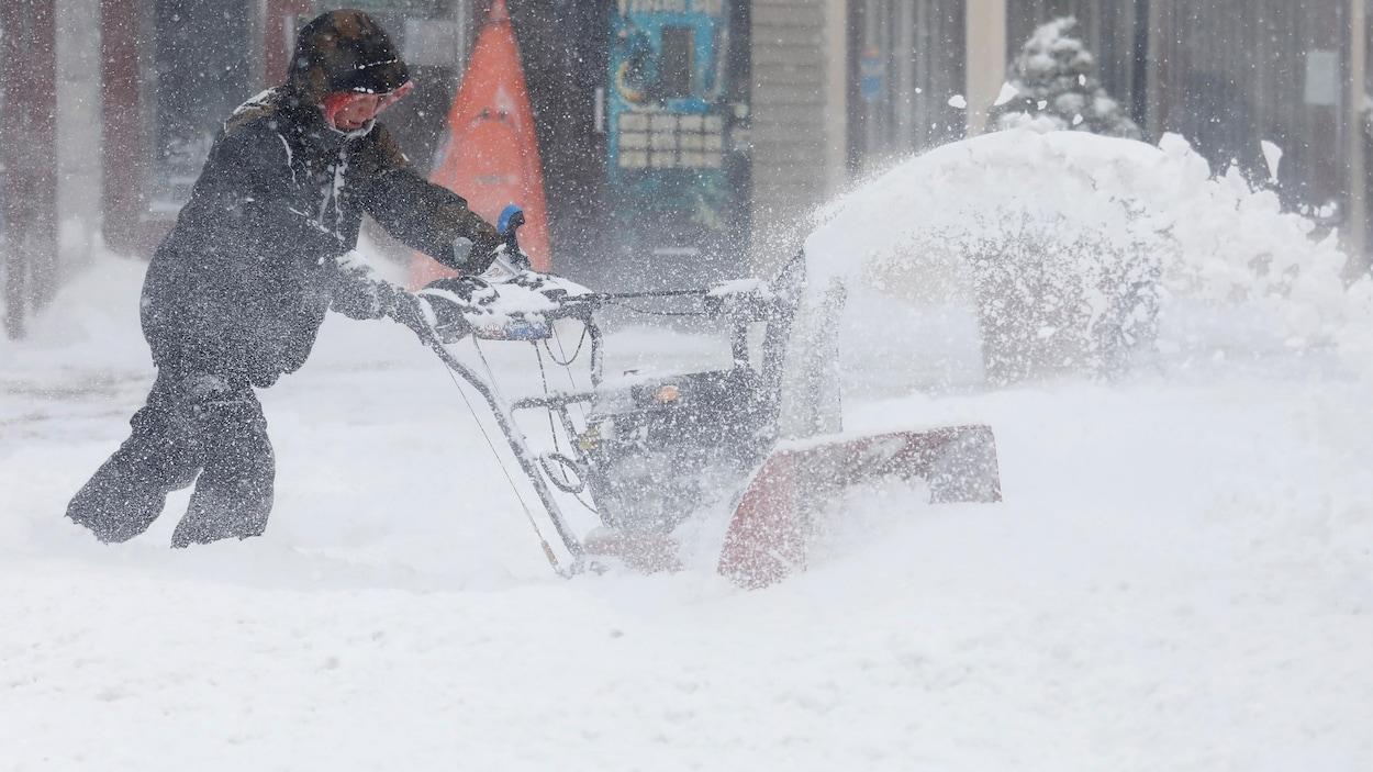 Un homme utilise une souffleuse à neige à Port Washington à New York.
