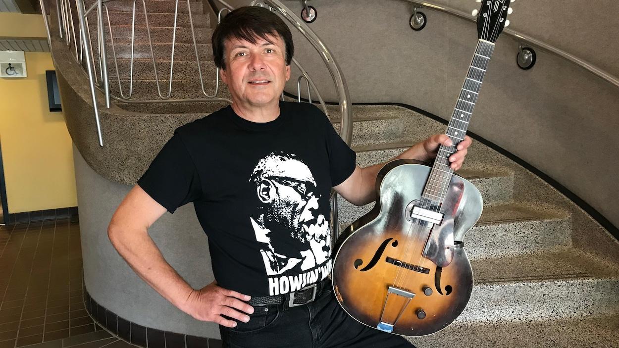 Marcel Soulodre vêtu de noir, debout avec une guitare à la main.