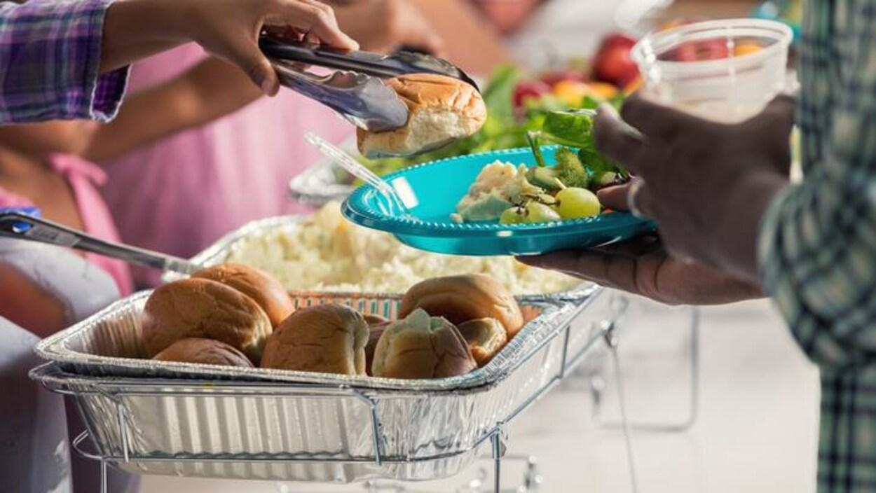Deux personnes dont l'une a une assiette remplie de nourriture.