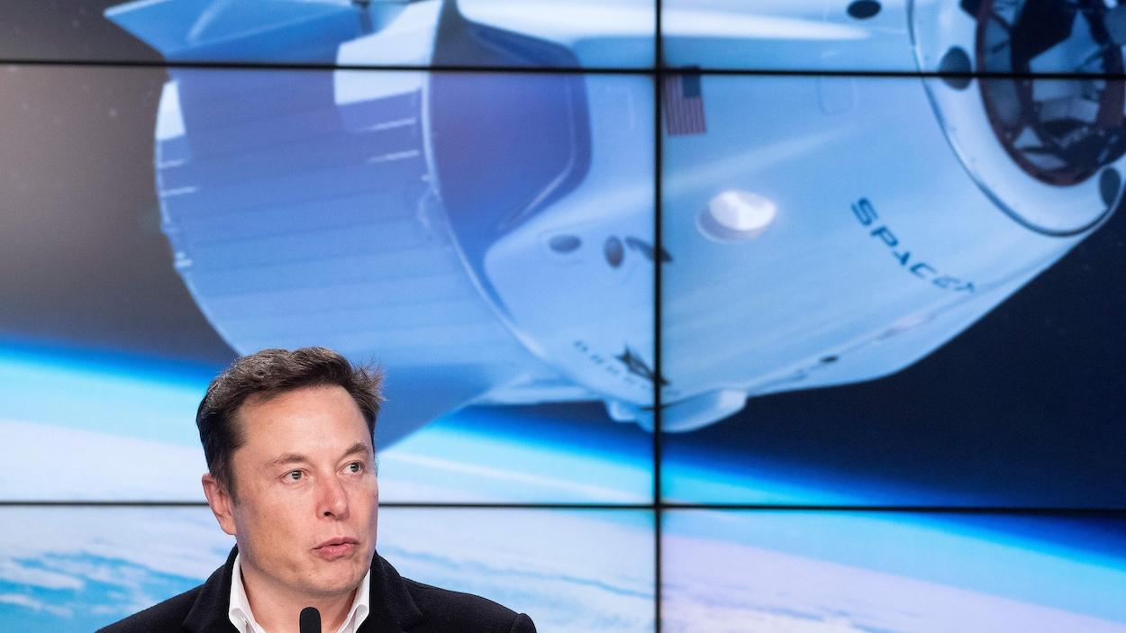 Elon Musk devant des écrans affichant une capsule spatiale de SpaceX en orbite.