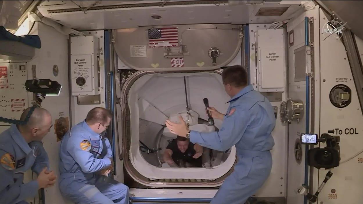 L'astronaute, en suspension, passe par un sas pour rejoindre les trois astronautes déjà sur place qui l'attendent.