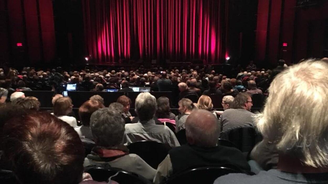 Le public assis, attend l'ouverture du rideau de scène.