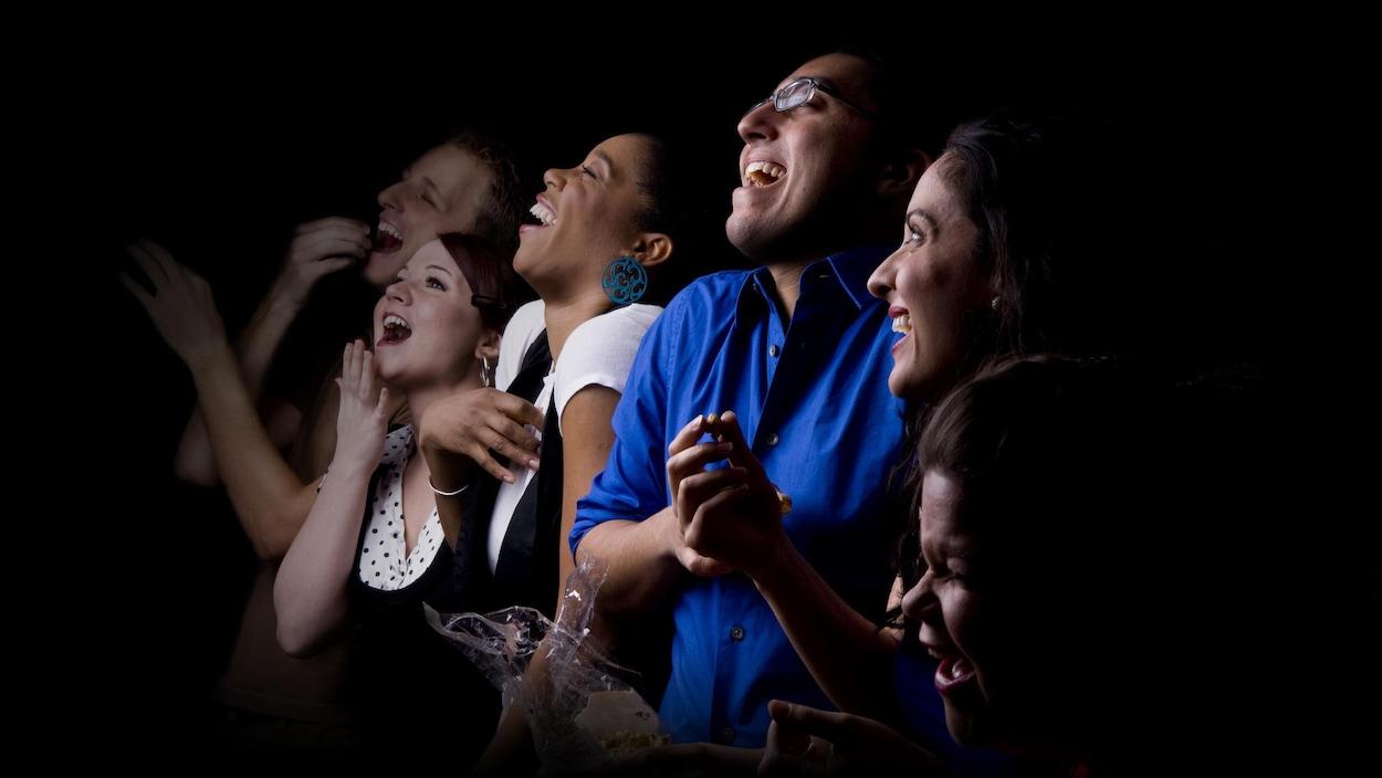 Plusieurs personnes rient en regardant un spectacle.