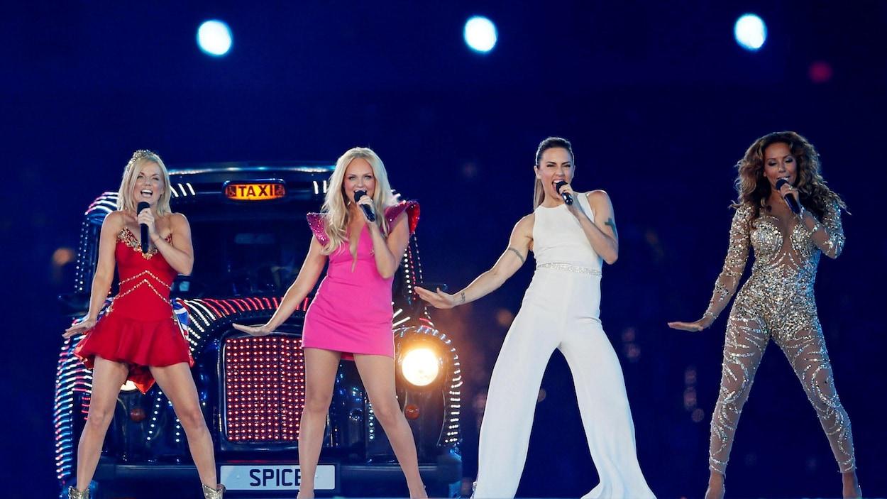 Geri Halliwell, Emma Bunton, Melanie Chisholm et Melanie Brown chantent sur scène.