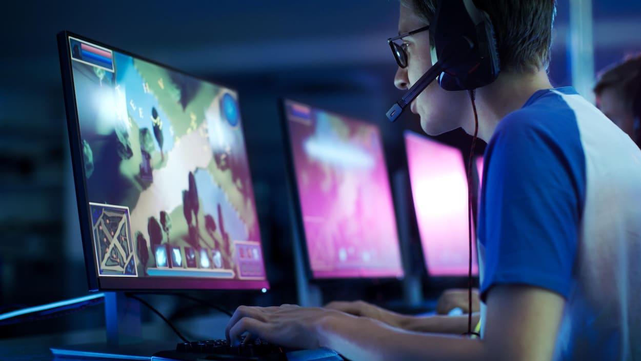 Un jeune homme joue à un jeu vidéo à l'ordinateur. Il porte un casque d'écoute équipé d'un micro ajustable pointé vers sa bouche.