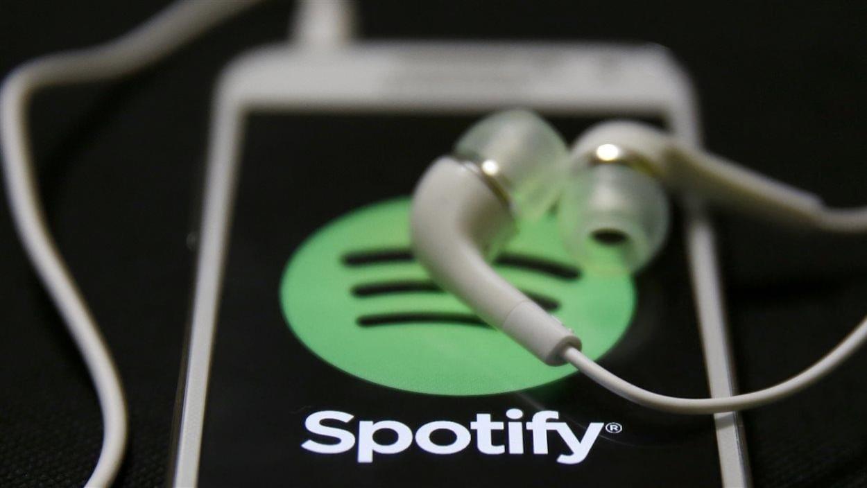 Des écouteurs reposent sur l'écran d'un téléphone intelligent affichant le logo de Spotify.