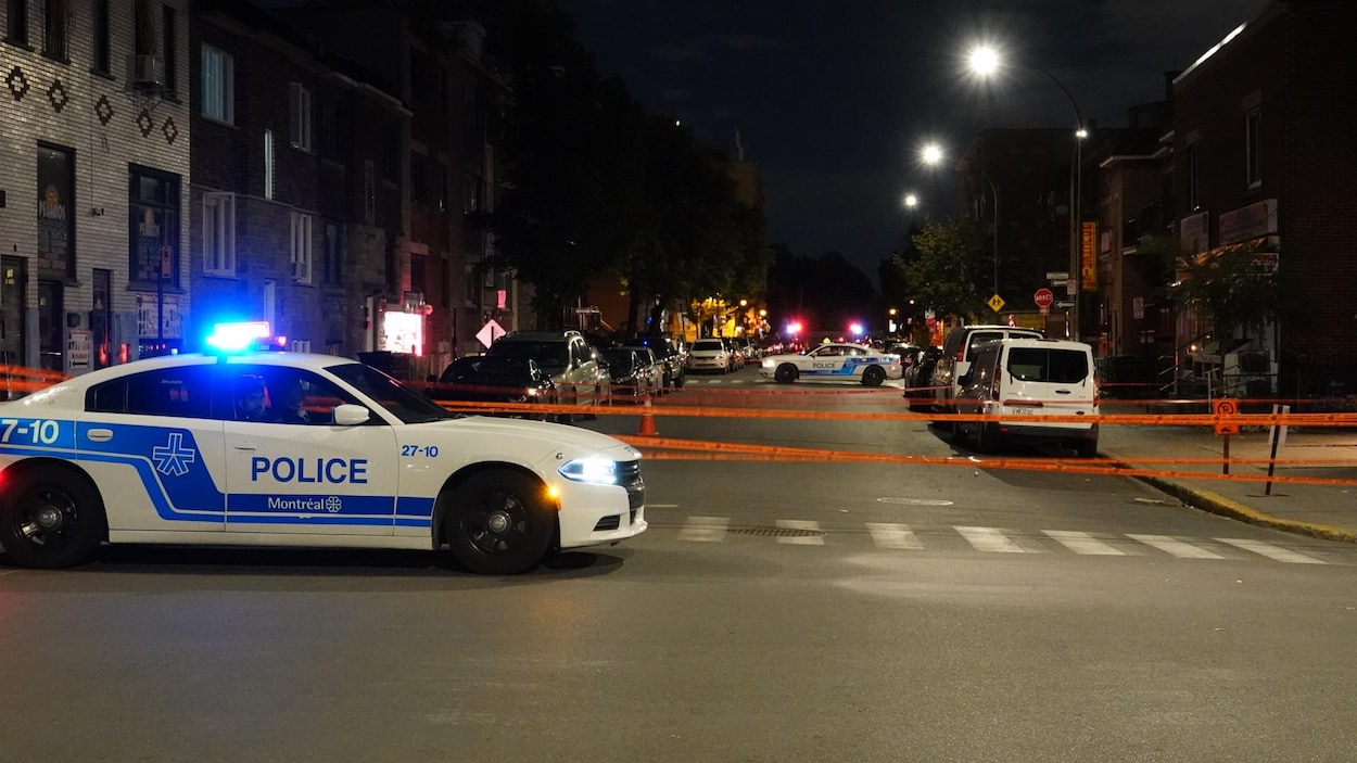 Deux voitures de police et des rubans de sécurité délimitent la scène où s'est produite l'agression.