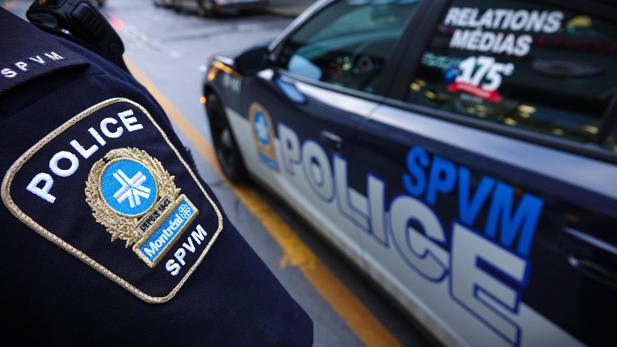 Un policier arbore son écusson d'épaule devant une voiture aux couleurs du SPVM.