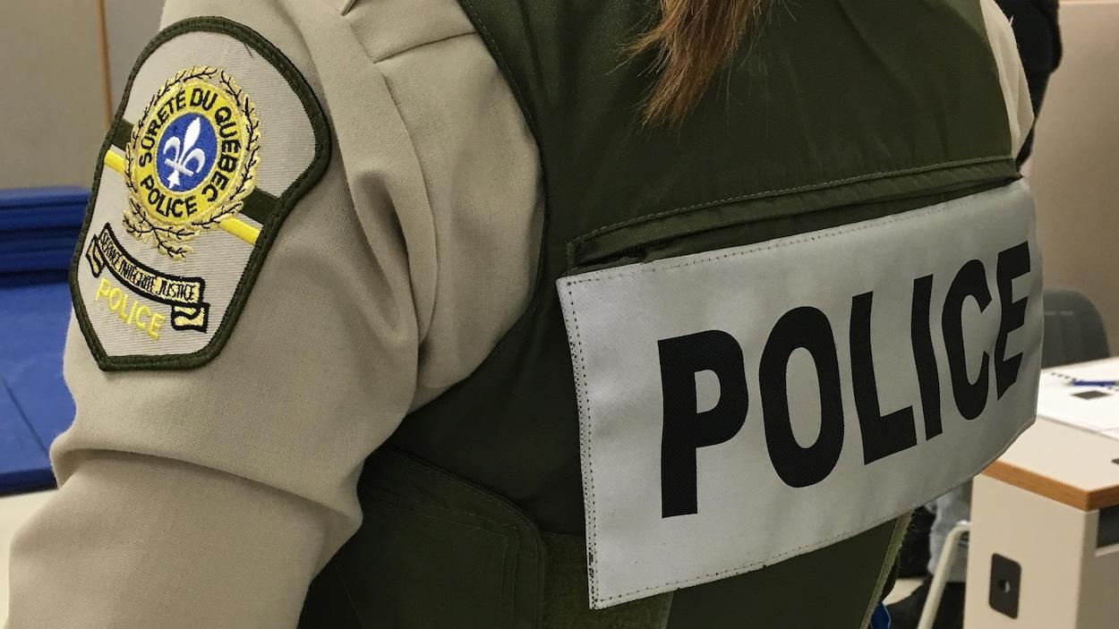 Inscription du mot police sur le dos d'une uniforme que porte une policière de la Sûreté du Québec