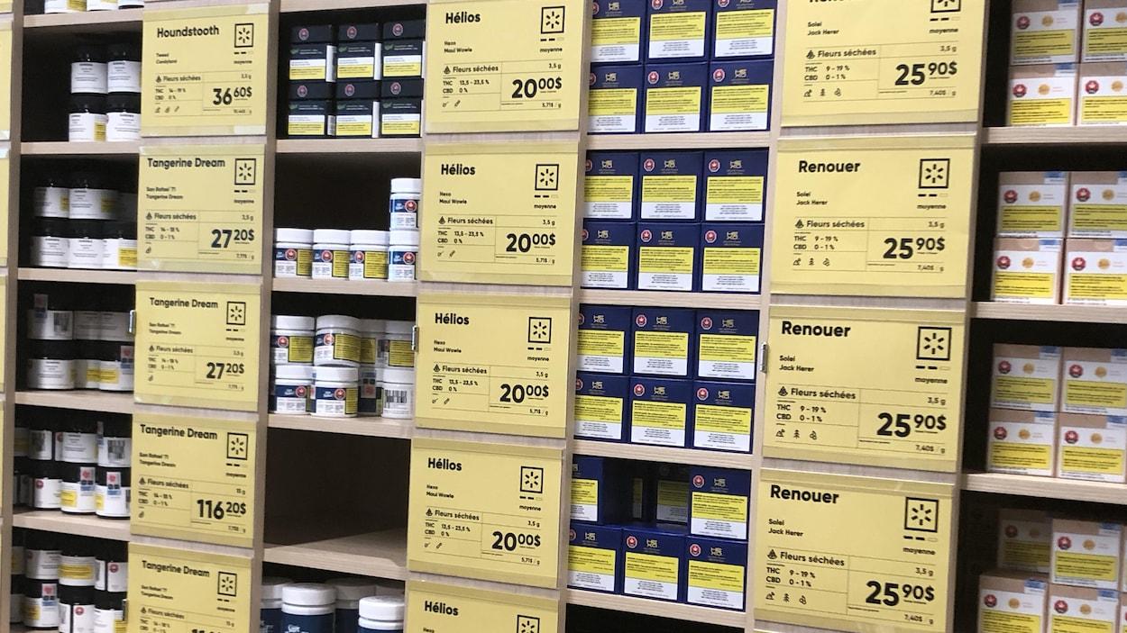 Des étagères remplies de produits avec les affiches montrant les prix.
