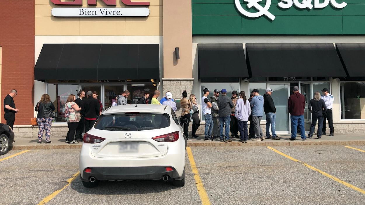 Une ligne de personnes devant un commerce de cannabis.