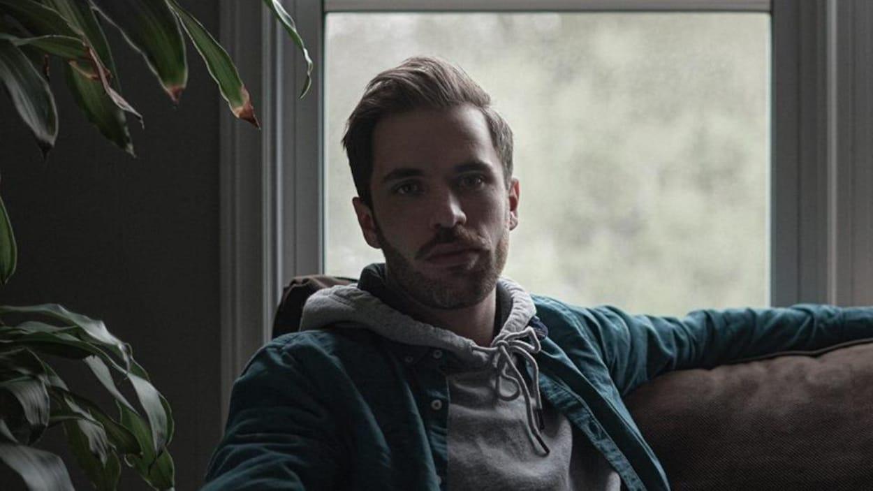 Un jeune homme est assis sur un sofa et regarde la caméra.