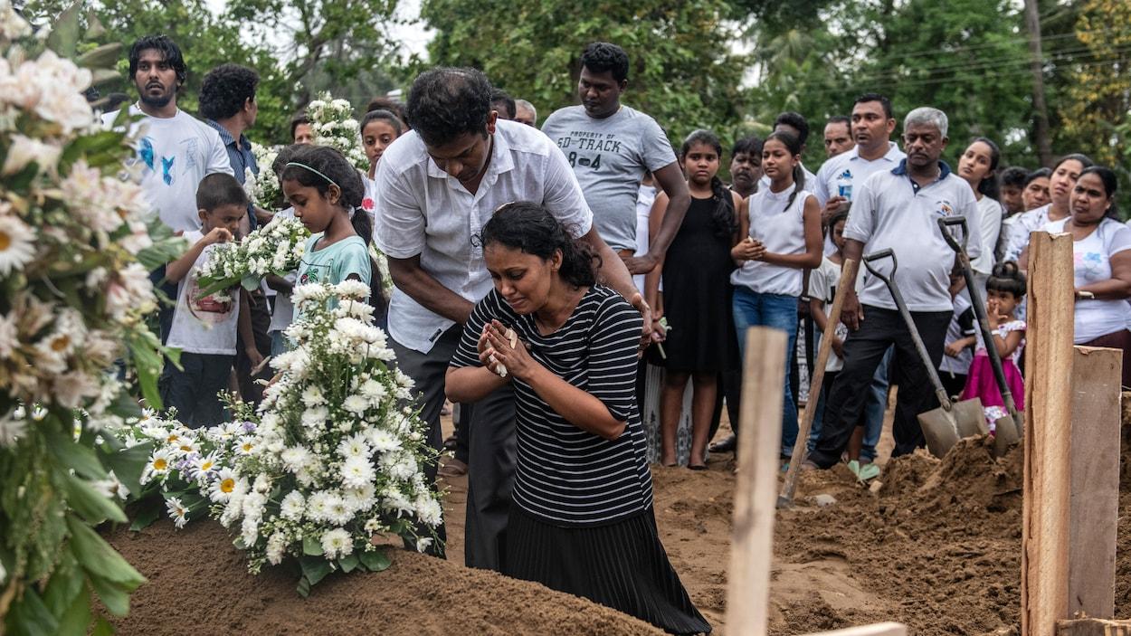 Une femme agenouillée pleure et se recueille sur la tombe d'une victime de l'attentat. Un homme la tient par les épaules, en guise de soutien.