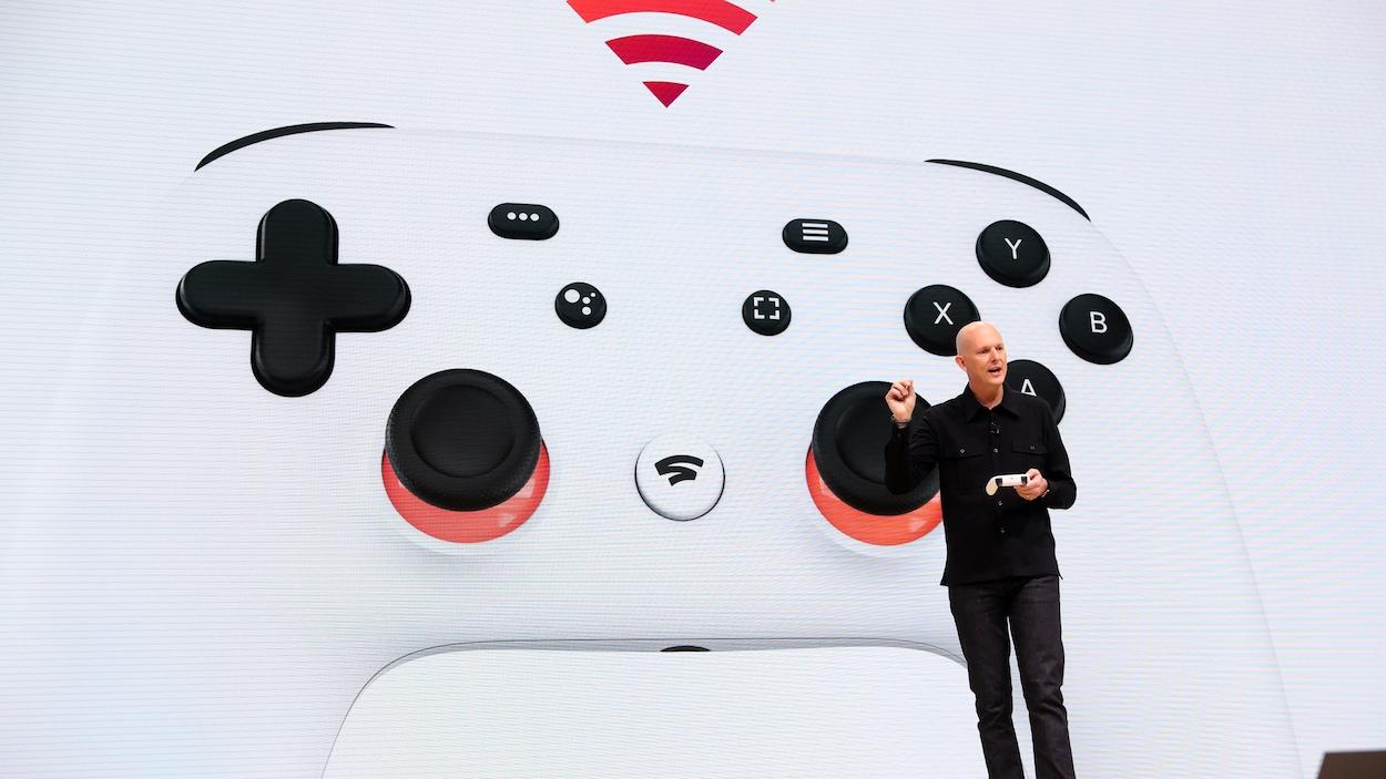 Le vice-président et directeur général de Google Phil Harrison tient la manette du système de jeux vidéo en flux en continu Stadia sur scène, devant une immense projection de celle-ci, lors d'un événement en mars 2019.