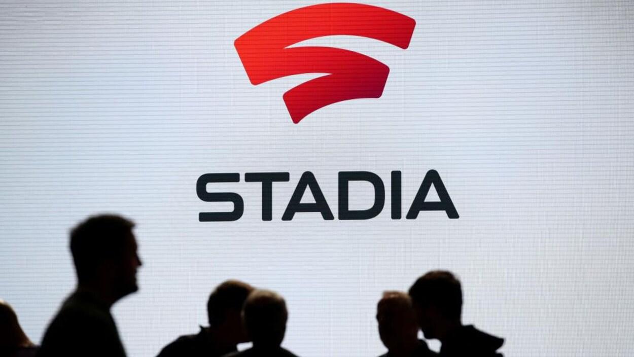 Des gens sont devant un écran, où est affiché le logo de Sadia.