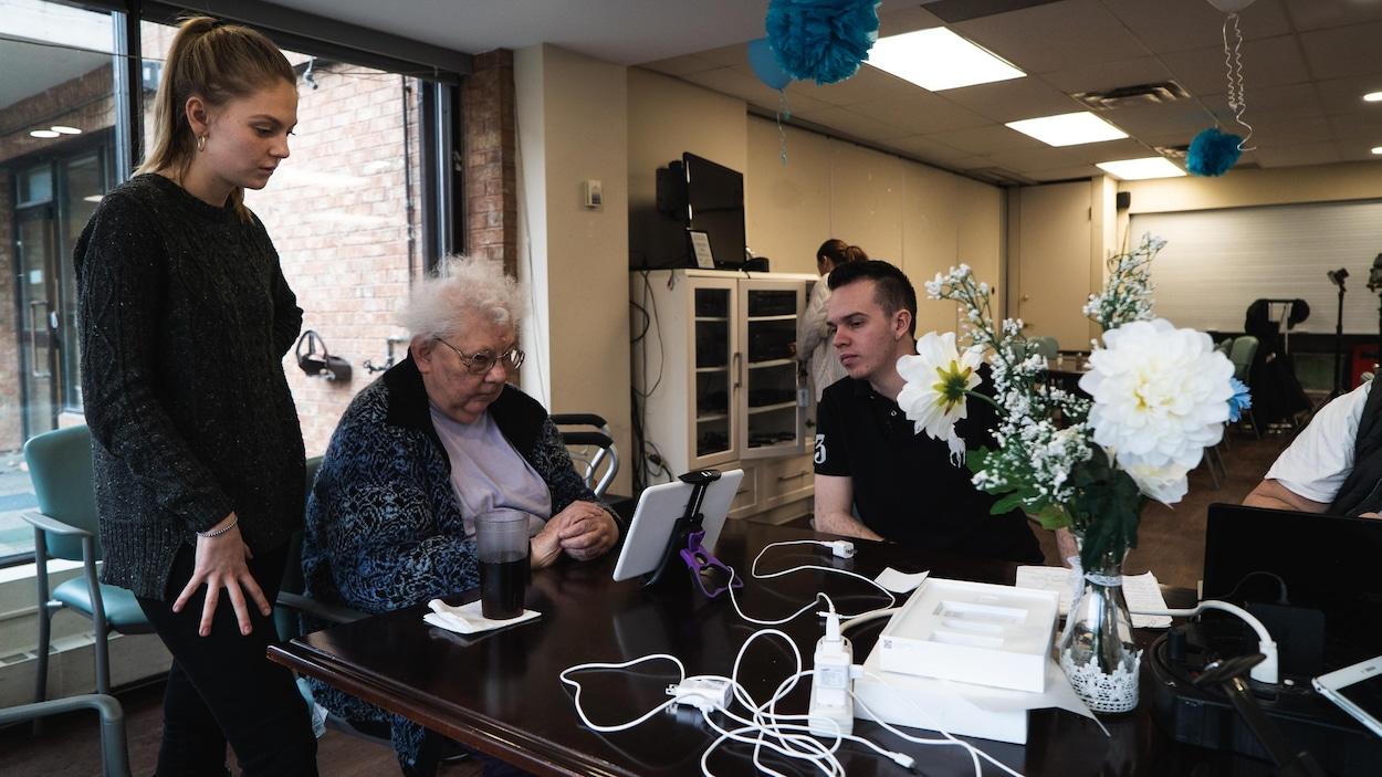 Une jeune femme et un jeune homme donne des conseils à une dame âgée assise devant une tablette.