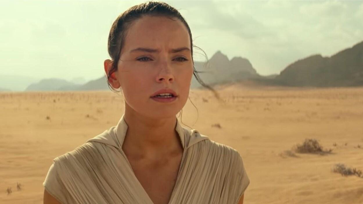 La jeune femme est au milieu d'un décor désertique.