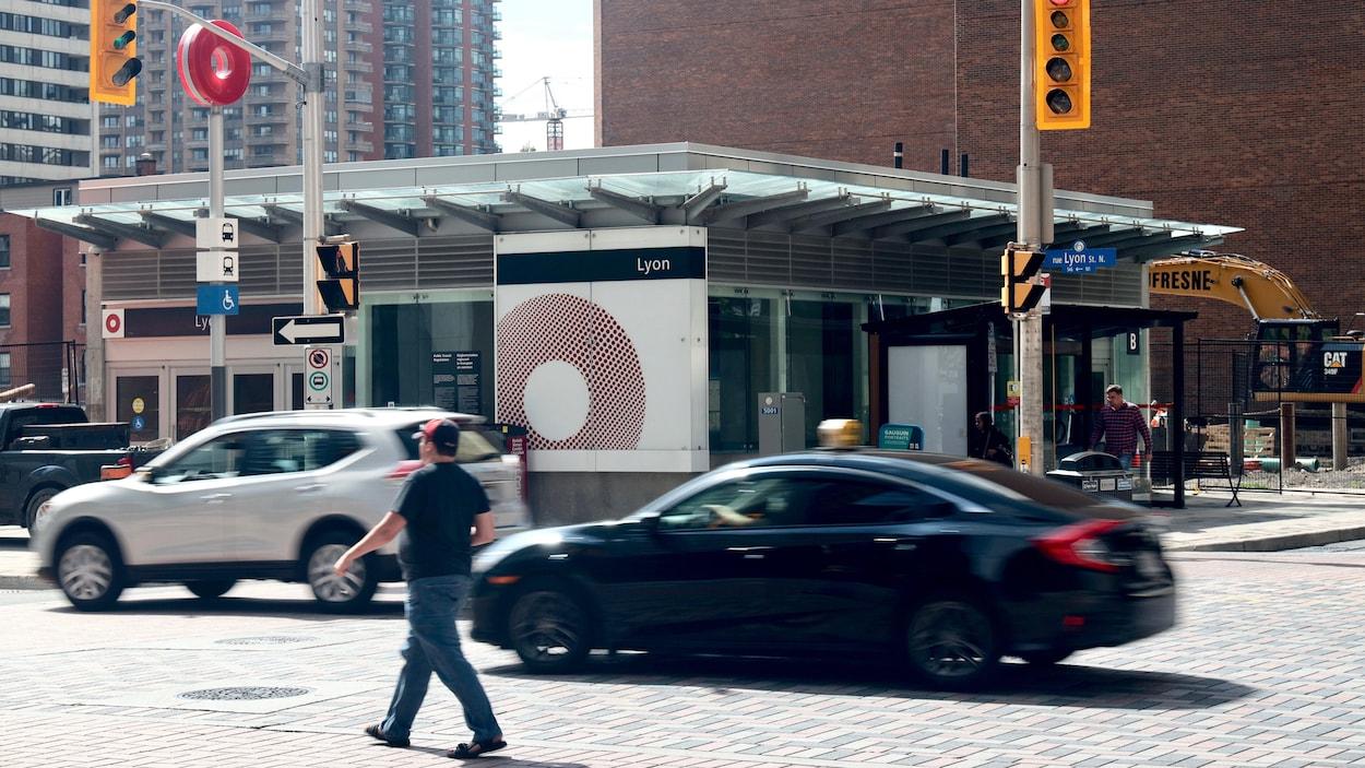 Des voitures et un piéton circulent devant un bâtiment abritant une station du train léger d'Ottawa.