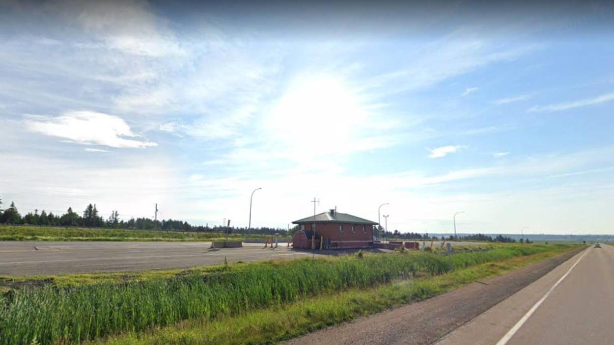 Une petite construction en briques entre deux voies de l'autoroute.
