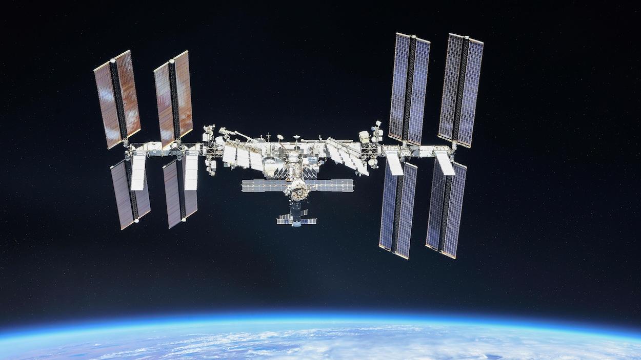 La Station spatiale internationale en orbite dans l'espace, au-dessus de l'horizon terrestre.