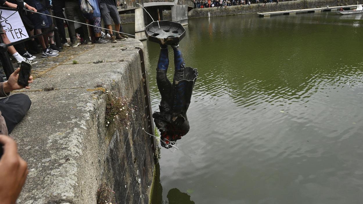 Une statue, tête en bas, en retenue par des cordes par des manifestants. Ils s'apprêtent à la jeter dans une rivière.