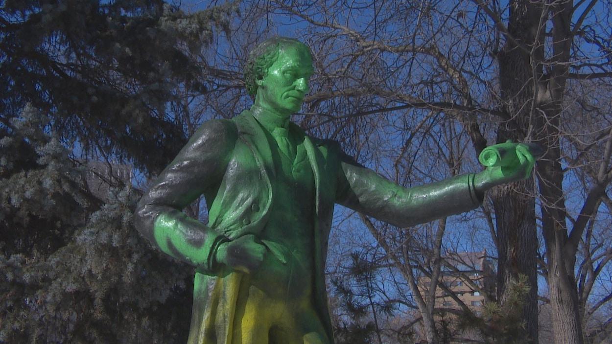 Le haut du corps de la Statue du premier premier ministre du Canada, John A. Macdonald est peint en vert. On voit également de la peinture jaune sur les pantalons de la statue.